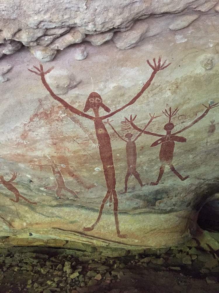 The main figure in this photo is a Timara known as 'the big boss of everybody, white man too', as told by an aboriginal elder. The larger figures to the right with the headdresses and their arms raised are cultural heros.