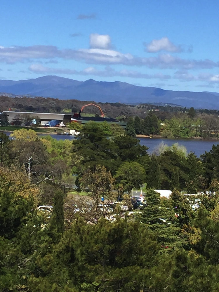 Canberra from the Floriade ferris wheel. Looking over Lake Burley Griffin, past the National Museum (the orange arch (mid-background) towards the hills.