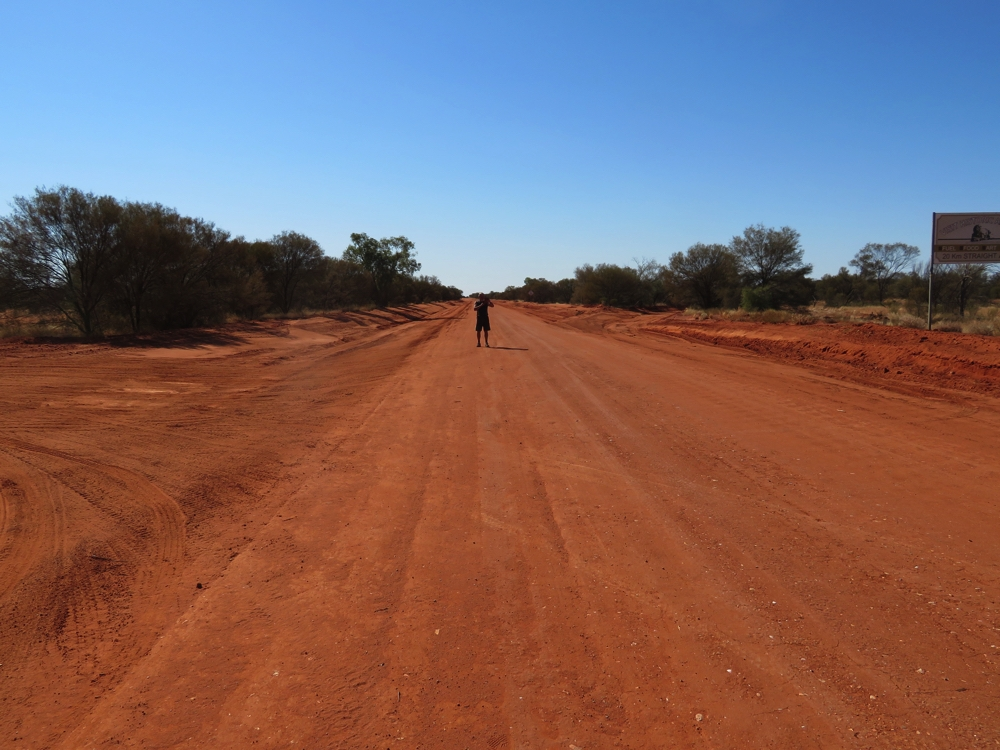 No idea what Ken is doing walking along this dusty red road.