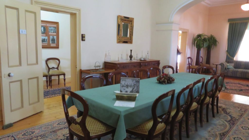 The dining room in Hoover House. The thing that looks like a cake tin at this end of the table is a replica of a gold bar. At an investors dinner in the early 1900s Hoover had real ones on the table to demonstrate the prosperity of this mine. Gwalia