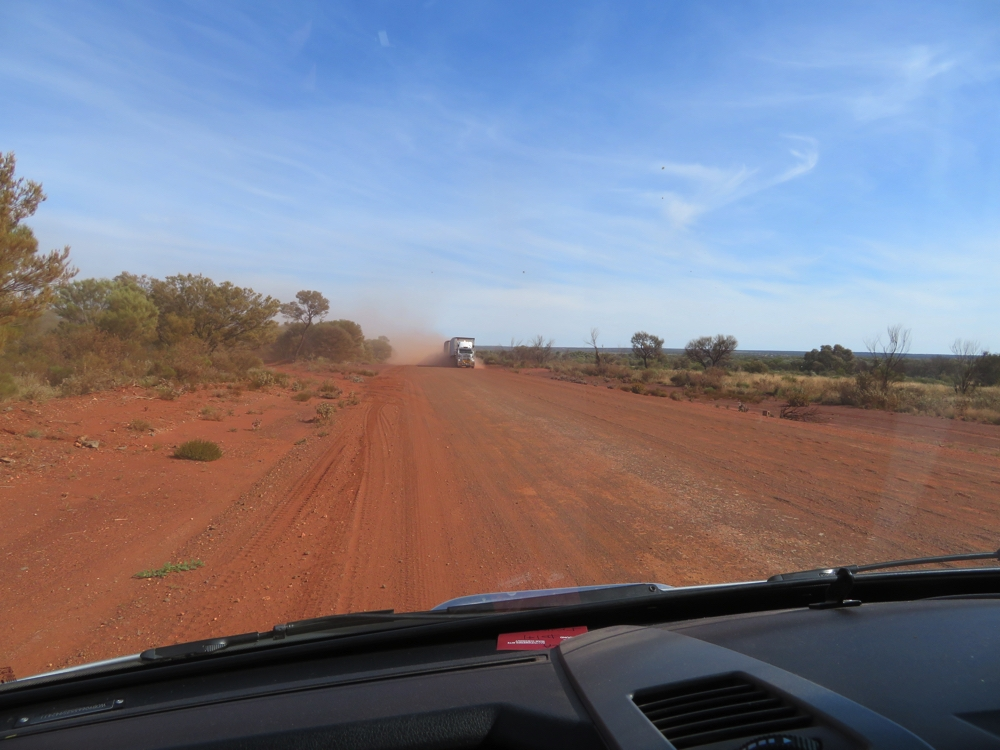 The cloud of dust that accompanies road trains is not fun. Pull over and stop - visibility too poor to keep driving.